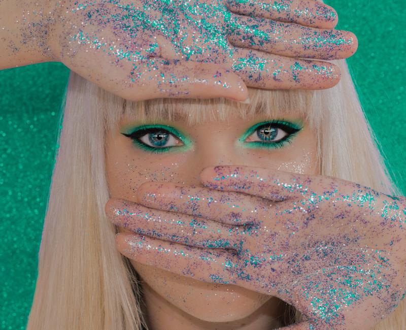 Eine Frau hat blauen Glitzer an den Handflächen und hält sich diese vor das Gesicht