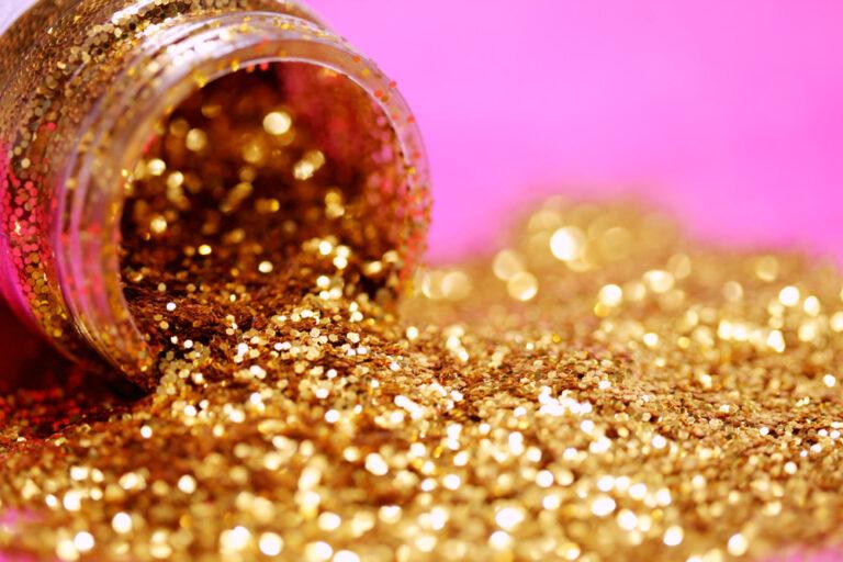 Aus einem Döschen fällt goldener Glitzer