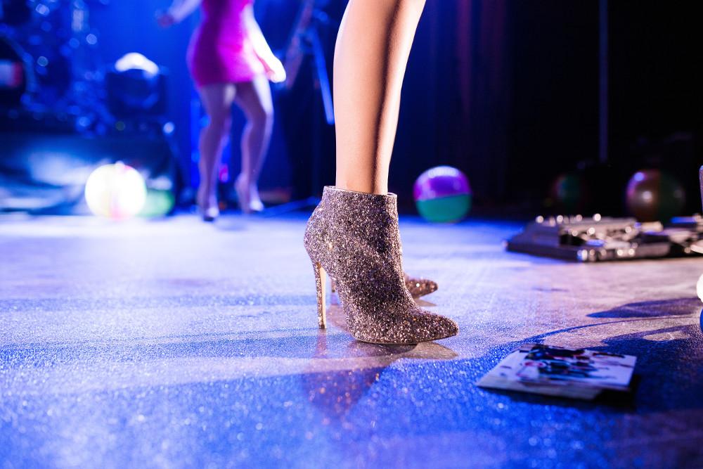 Jemand steht in glitzernden High-Heel-Stiefeletten auf einer Tanzfläche