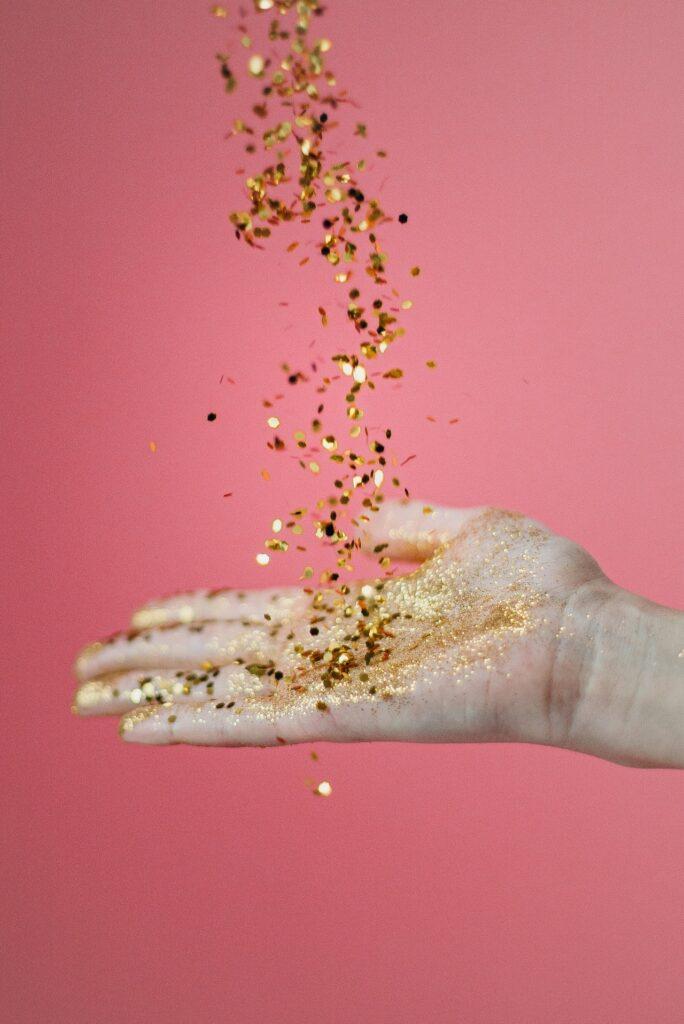 Auf eine Hand fallen goldene Glitzerpartikel