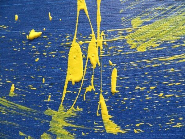 Auf einem blauen Untergrund sind gelbe Farbkleckse
