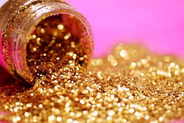 Ein Döschen Glitzer ist geöffnet und goldene Partikel fallen heraus