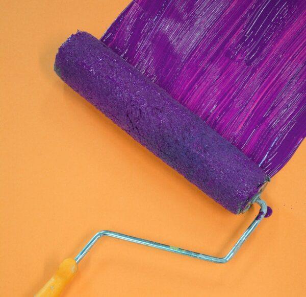 Eine Lackwalze verteilt lila Farbe auf einem orangenen Untergrund