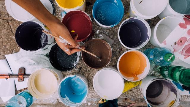 Verschiedene Farbeimer sind geöffnet. Eine Hand taucht einen Pinsel in einen der Töpfe ein.