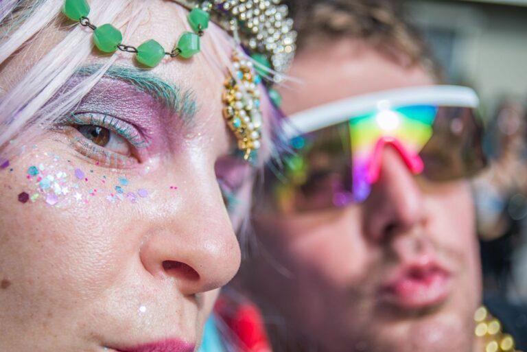 Zwei Menschen mit glitzernd-bunt verzierten Gesichtern beim Feiern.