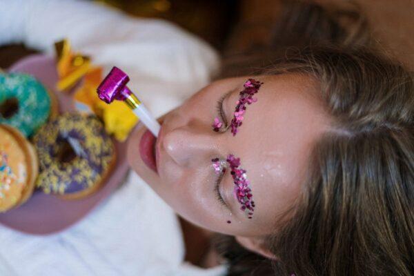 Eine Frau mit pink glitzernden Augenbrauen hat Donuts auf dem Schoß und eine Tröte im Mund