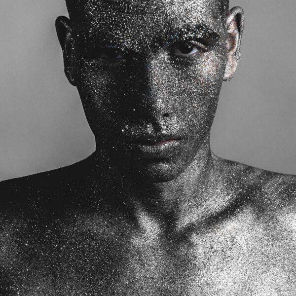 Ein Mann ist im gesamten Gesicht und auf dem Oberkörper gänzlich mit silbernem Glitzer bedeckt.