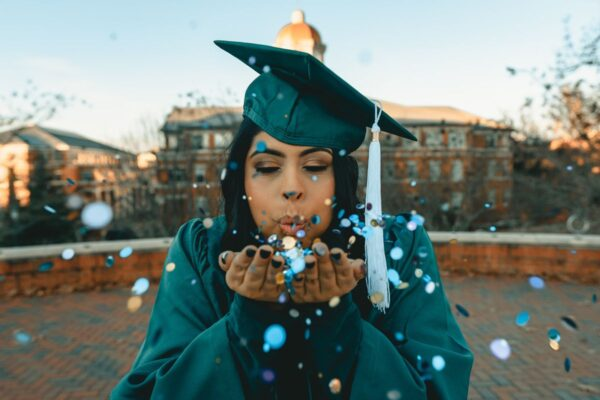 Eine junge Frau mit einer türkisen Absolventinnen-Robe ist zu sehen. Sie hat türkise Glitzerpertikel auf ihren Händen, welche Sie in Richtung des Betrachters pustet.