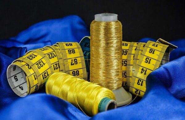 Auf blauem Stoff sind ein gelbes Maßband und zwei goldene Garne zu sehen