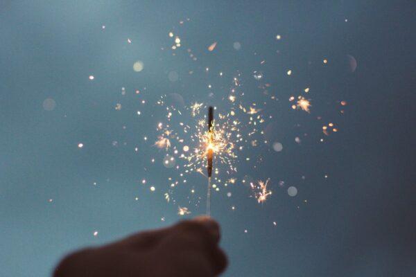 Auf einem Bild ist ein Teil einer Hand im Dunklen zu sehen, die eine funkelnde Wunderkerze hält.