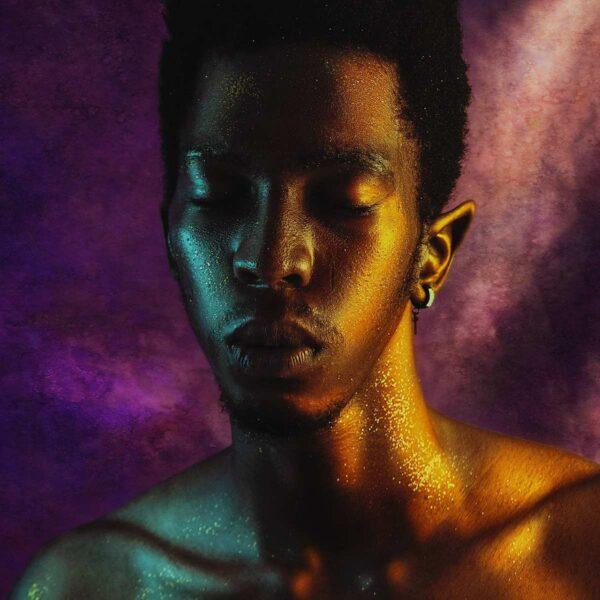 Ein Portrait eines schwarzen Mannes, der goldenes Glitzer-Makeup im Gesicht hat