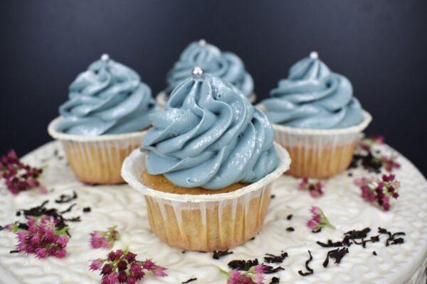 Auf einem weißen Untergrund, auf dem Blütenblätter verstreut sind, stehen vier Muffins mit blauer Cremehaube. Auf der Cremehaube ist silberfarbener, essbarer Glitzer sowie eine Silberkugel auf der Spitze zu sehen.