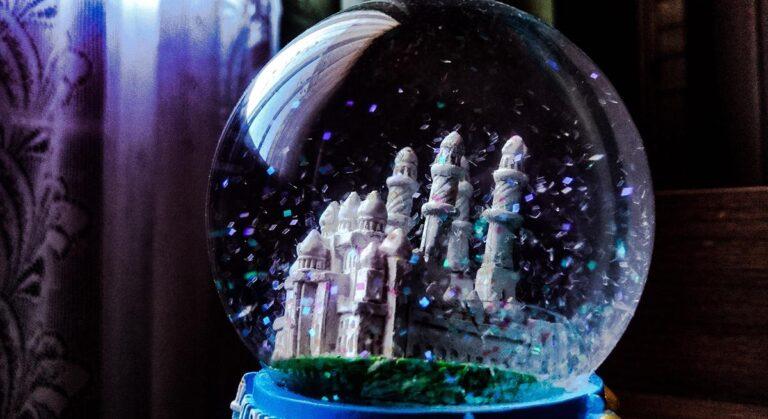 Ein zauberhaft anmutendes Schloss in einer Schneekugel, auf das irisierend funkelnder Glitzer rieselt.