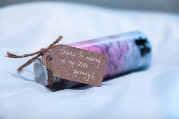 Ein längliches Fläschchen mit Watte und Glitzer darin. Daran hängt ein Geschenkkärtchen aus Pappe.
