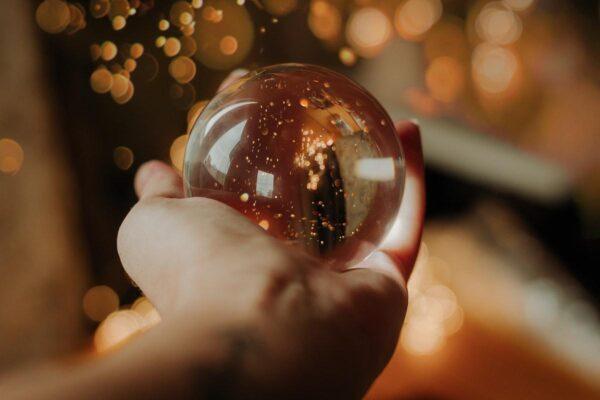 Eine Hand, die eine durchsichtige Glaskugel hält, in der goldener Glitzer funkelt.