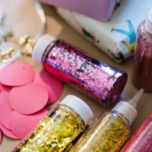 Auf einem Tisch liegen Bastelmaterialien, darunter mehrere Flaschen Glitzerkleber und Streuglitter in Gold- und Rosatönen.