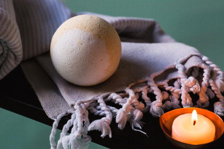 Auf einer Bank liegt eine Decke mit einer Badebombe obendrauf und einer Kerze daneben