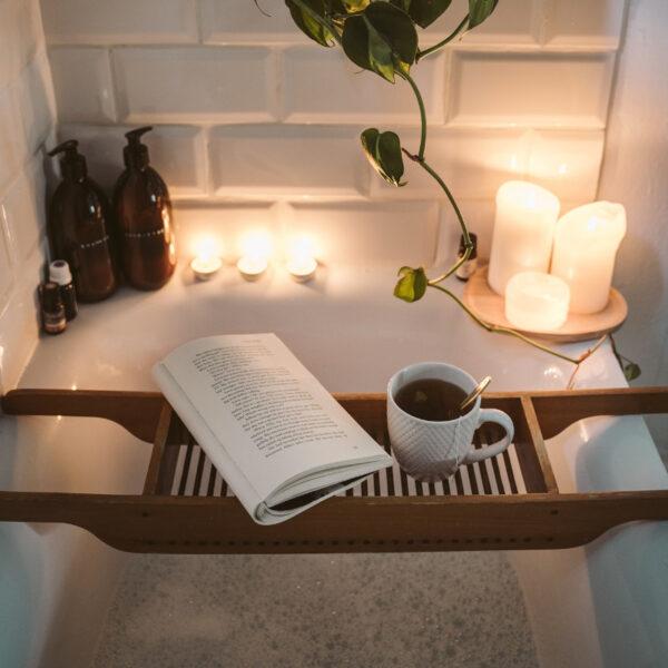 Über eine Badewanne wurde ein kleines Tablett mit einem Buch und einer Tasse darauf gelegt. Am Rand stehen Essenzen und Kerzen