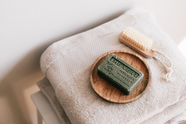 Auf einem Handtuch liegt ein Stück Seife und eine Bürste