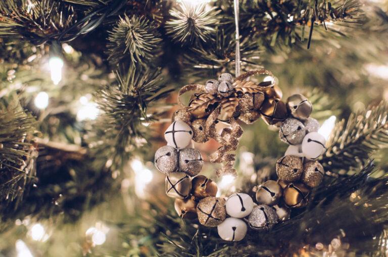 Ein Weihnachtskranz aus glitzernden Glocken hängt an einem Tannenbaum