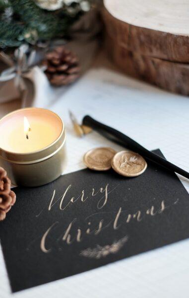 """Neben etwas Deko und einer Kerze liegt eine schwarze Weihnachtskarte mit dem goldenen Schriftzug """"Merry Christmas"""""""