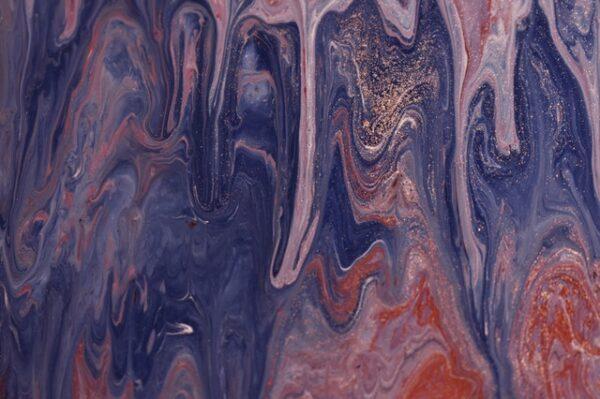 Auf einer Oberfläche verlaufen verschiedene Rosé- und Violetttöne ineinander und wurden mit goldenem Glitzer verziert