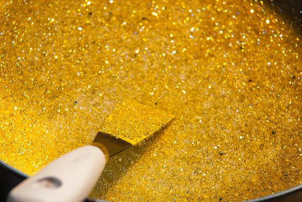 Ein Spachtel fährt über eine gold-beglitterte Oberfläche