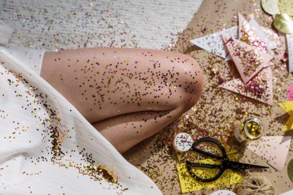 Auf einem Bein sowie dem Boden und Bastelutensilien ist jede Menge goldener Glitzer verteilt