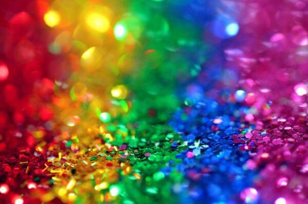 Einige Glitzerpartikel sind in den Farben des Regenbogens nebeneinander angeordnet