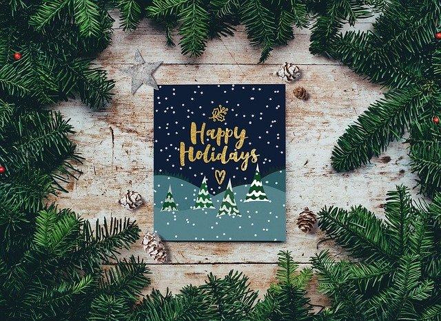 """Zwischen einigen Tannenzweigen liegt eine Weihnachtskarte mit einem goldenen Schriftzug """"Happy Holidays"""""""