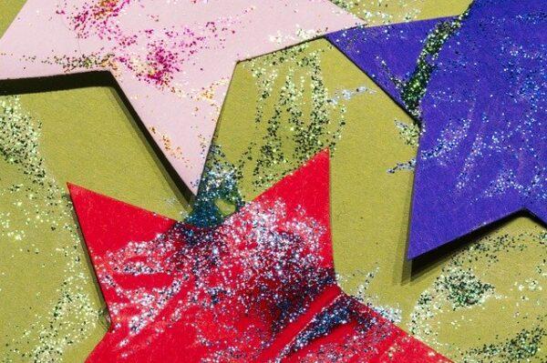 Einige bunte Papiersterne wurden mit verschiedenfarbigem Glitzer bestreut