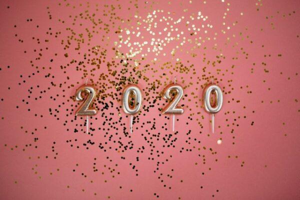 Eine pinke Wand wurde mit goldenem Glitzer besprenkelt. Davor hängen goldene Luftballons, welche 2020 lesen