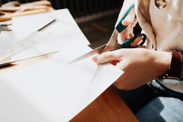 Mit einer Schere wird ein Blatt Papier durchgeschnitten