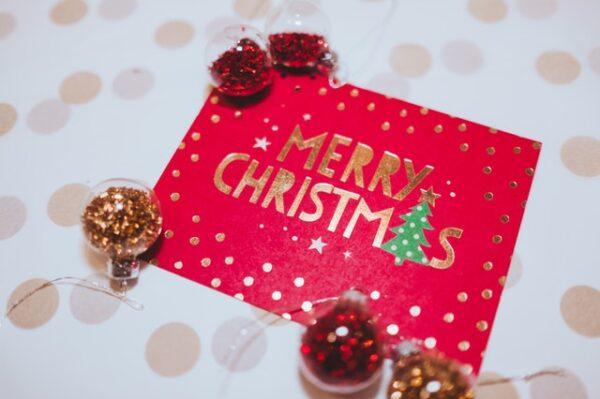 Eine rote Weihnachtskarte neben der kleie Kugeln gefüllt mit Glitzer liegen