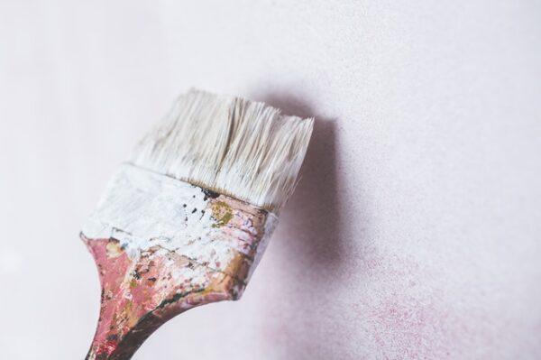 Mit einem Pinsel wird eine Wand weiß gestrichen