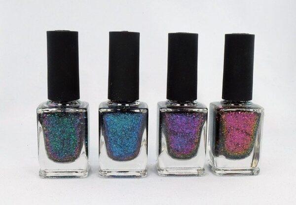 Nebeneinander stehen vier Glitzer-Nagellacke in unterschiedlichen Farben