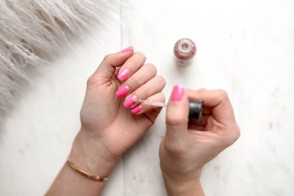 Eine Frau mit rosa Nägeln trägt einen glitzernden Klarlack auf