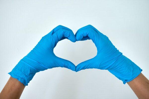 Hände, die Einweghandschuhe tragen, formen ein Herz