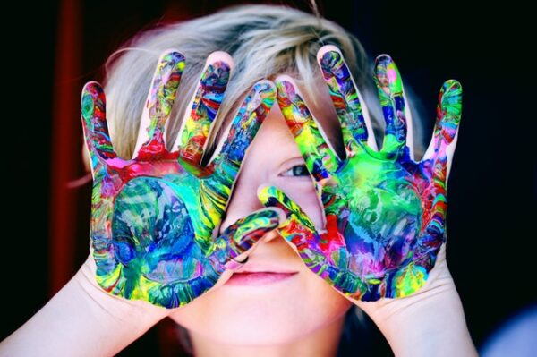 Ein Kind hält Hände, welche in Farbe getaucht wurden, in die Luft