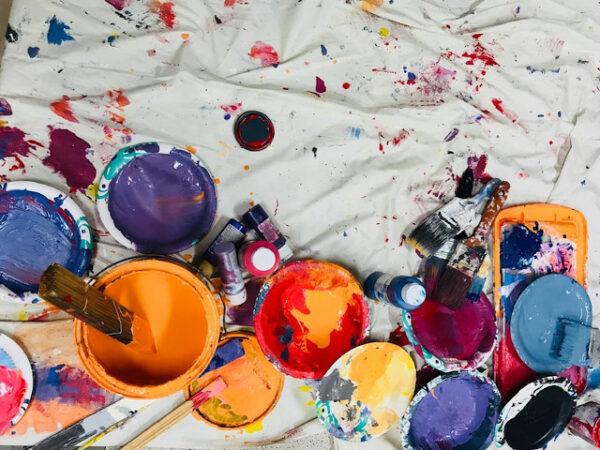 Einige Farbtöpfe sowie Pinsel liegen auf einem weißen Laken