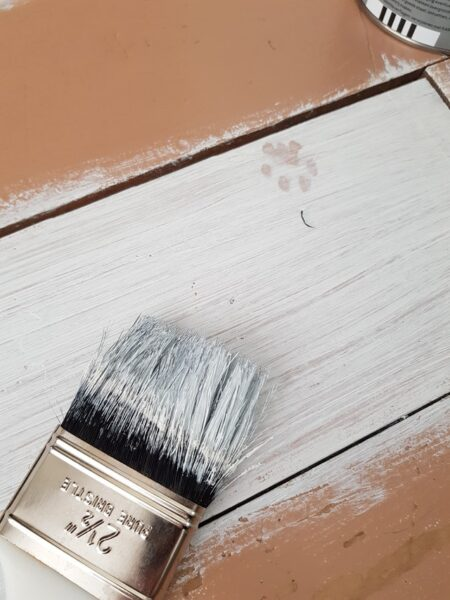 Ein Stück Holz wurde mit weißem Lack bestrichen
