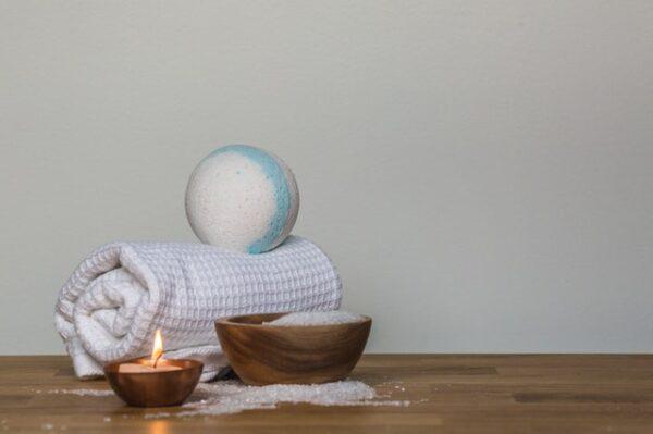 Eine Badekugel liegt auf einem Handtuch. Davor liegt etwas Badesalz und eine Kerze