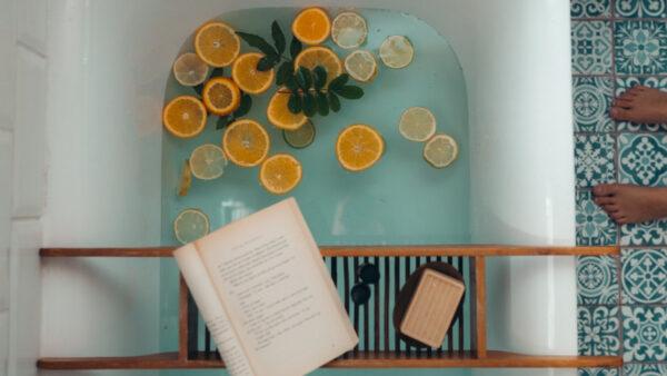 In einer Badewanne liegen einige Zitrusscheiben, darüber wurde ein Tablett mit einem Buch und einer Seife drapiert