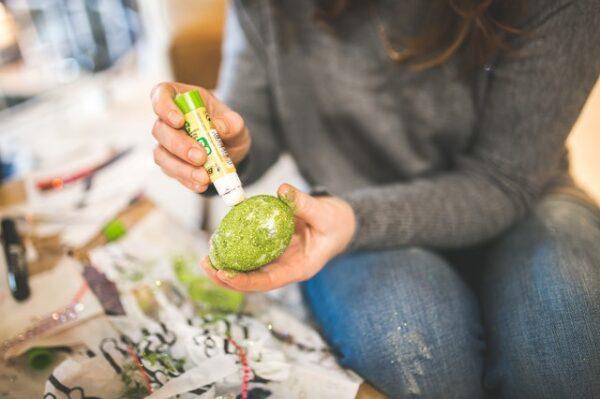 Eine Frau leimt ein Ei ein und bestreut es mit grünem Glitzer