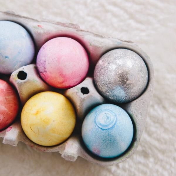 In einem Eierkarton liegen sechs bunte Eier