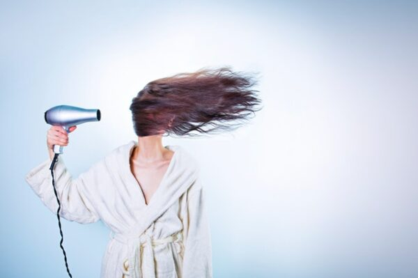 Eine Frau föhnt sich die Haare