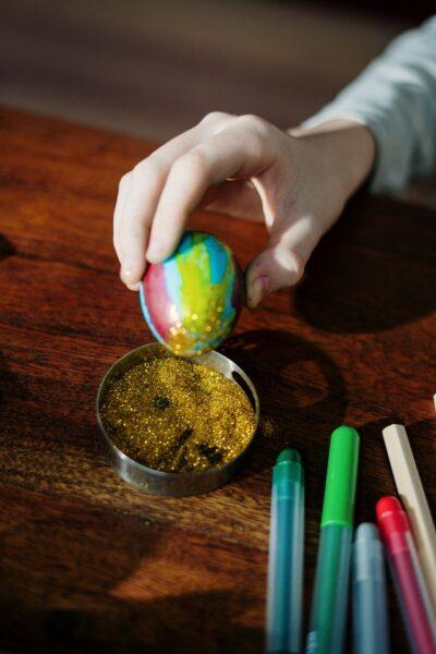 Jemand tunkt ein buntes Ei in goldenen Glitzer