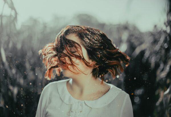 Eine Frau mit Bob und Glitzer-Ansatz schwingt ihr Haar