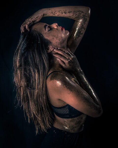 Eine Frau hat auf dem ganzen Körper goldenen Glitzer verteilt
