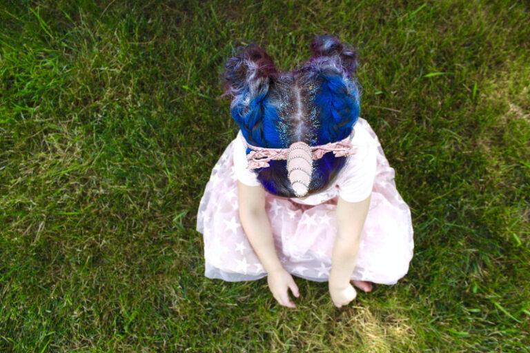 Ein kleines Mädchen in einem rosa Kleid hat blau-lilane Haare und einen Ansatz, welcher mit Glitzer verziert wurde